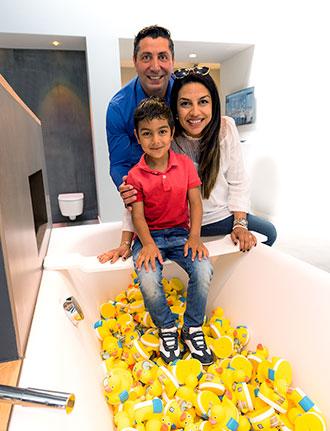 Freundliche Familie sitzt an Badewanne