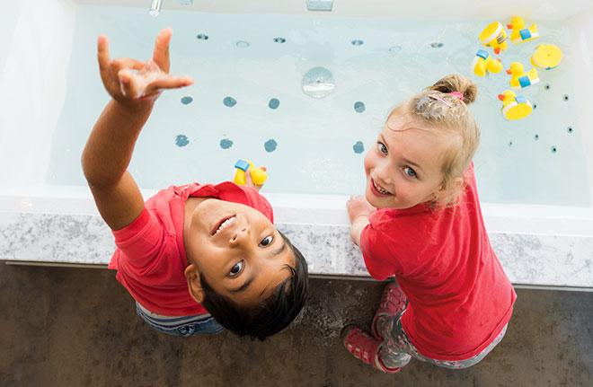 Kinder spielen an Badewanne